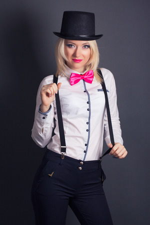tophat: beautiful young woman wearing tophat, bow-tie and braces against grey background
