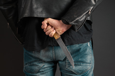 man hands with knife on gray background photo