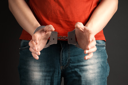 cuffed: man hands in handcuffs