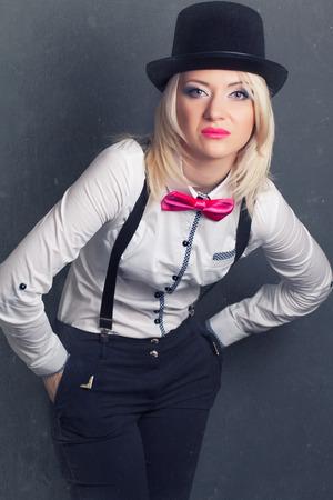 tophat: bella giovane donna che indossa tophat, bow-cravatta e bretelle contro sfondo grigio Archivio Fotografico