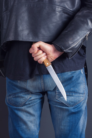 cuffed: man hands with knife on gray background Stock Photo