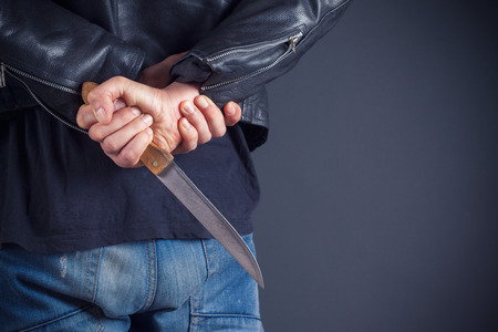 felony: man hands with knife on gray background Stock Photo
