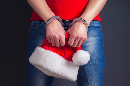 cuffed: man hands in handcuffs with red santa claus hat