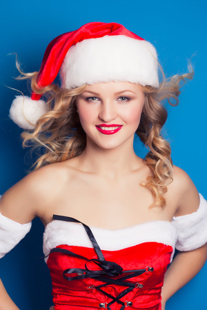 beautiful young woman wearing Santa Claus costume against blue background photo