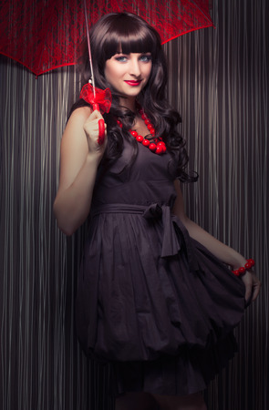 beautiful young woman posing with red lace umbrella against retro wallpapers photo