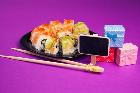 Maki sushi on purple background with blackboard