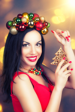 gold facial: beautiful woman wearing a wreath made from Christmas decorations and holding Christmas decorations