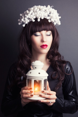 in vouge: beautiful young woman wearing designer wreath and holding white candle lamp