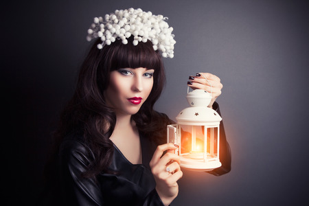 vouge: beautiful young woman wearing designer wreath and holding white candle lamp