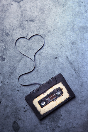 audio cassette with magnetic tape in shape of heart on grunge background