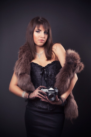 portrait of beautiful young retro woman holding vintage camera photo