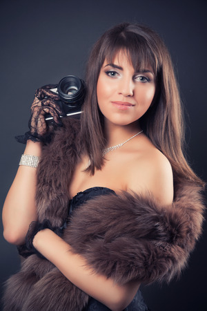 black boa: portrait of beautiful young retro woman holding vintage camera Stock Photo