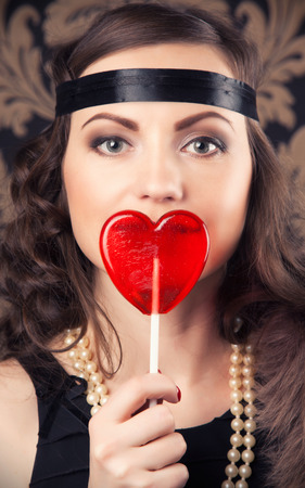 silent film: beautiful retro woman holding red heart-shaped lollipop against vintage wallpapers