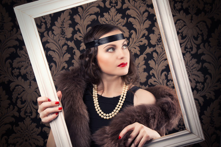silent film: beautiful retro woman posing with white wooden frame against vintage wallpapers Stock Photo