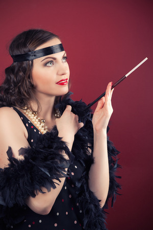 black boa: beautiful retro woman holding mouthpiece against wine red background Stock Photo