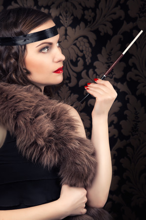 black boa: beautiful retro woman holding mouthpiece against vintage wallpapers Stock Photo