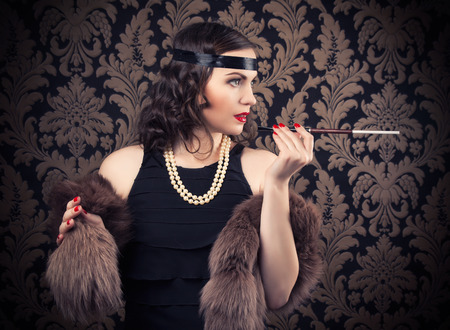 silent film: beautiful retro woman holding mouthpiece against vintage wallpapers Stock Photo