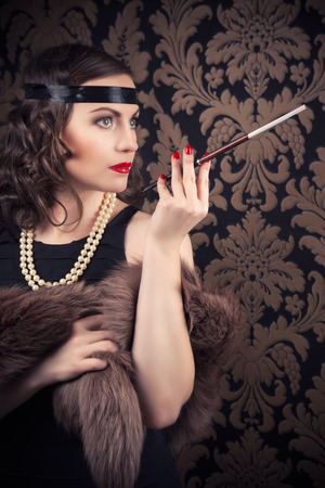 mouthpiece: beautiful retro woman holding mouthpiece against vintage wallpapers Stock Photo