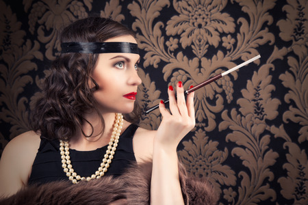 thirty���s: beautiful retro woman holding mouthpiece against vintage wallpapers Stock Photo