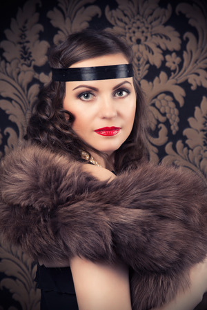silent film: beautiful retro woman posing against vintage wallpapers Stock Photo