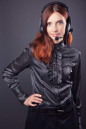 simultaneous: beautiful business woman with headphones against dark grey background Stock Photo