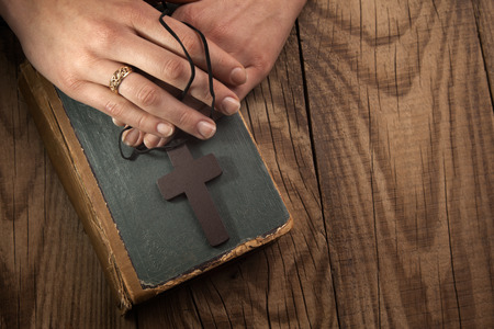 missionary: closeup of hands holding vintage cross on Bible