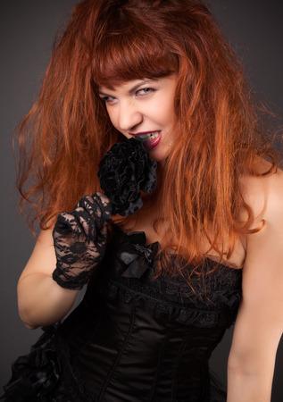 victorian girl: gothic redhead woman in sexy black satin corset against dark grey background Stock Photo