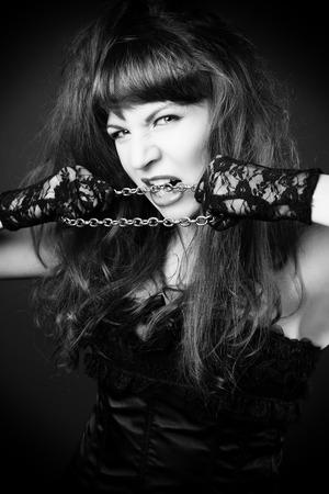 black satin: gothic redhead woman in sexy black satin corset against dark grey background Stock Photo