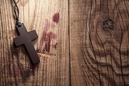 crucify: Cross on wooden background with stains of blood Stock Photo
