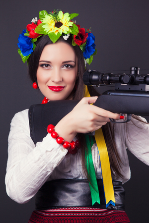 airgun: beautiful young woman wearing national ukrainian clothes and holding a rifle Stock Photo