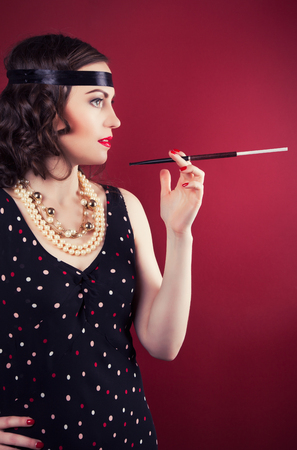 silent film: beautiful retro woman holding mouthpiece against wine red background Stock Photo