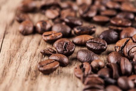 grano de cafe: Granos de café en el fondo de madera