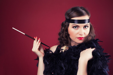 mouthpiece: beautiful retro woman holding mouthpiece against wine red background Stock Photo