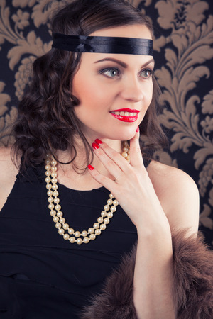 retro woman: beautiful retro woman posing against vintage wallpapers Stock Photo