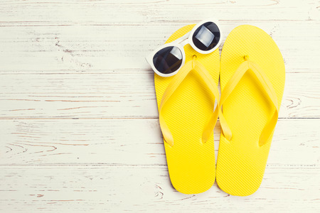 flip flops: Yellow flip flops and sunglasses on a white wooden background Stock Photo