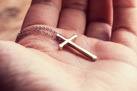 Silver cross in a hand  close up image