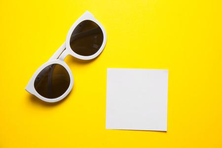 gafas de sol: Gafas de sol blancas con estilo en fondo amarillo con marcos de papel blanco Foto de archivo