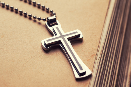 religions: Closeup of silver Christian cross on bible
