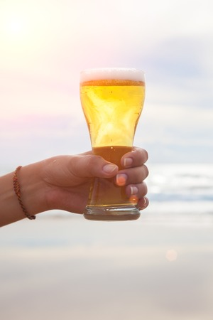 thirsting: Young woman hand holding a refreshing beer on the beach