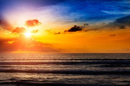 Mooie oranje zon opkomen met de zee en wolken Stockfoto