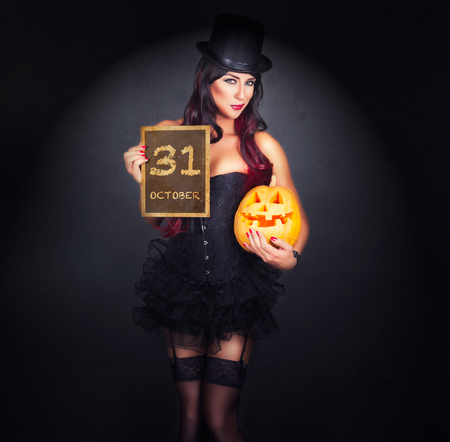 gothic fetish: Beautiful witch in black gothic Halloween costume holding Jack-o-lantern in hands with blackboard