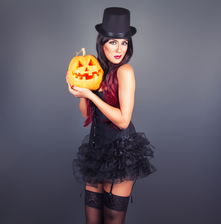gothic fetish: Beautiful witch in black gothic Halloween costume holding Jack-o-lantern in hands