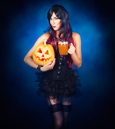 dark face: Beautiful witch in black gothic Halloween costume holding Jack-o-lantern in hands and beer