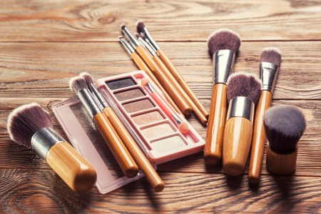 chaotically: Brushes with cosmetics scattered chaotically on wooden background