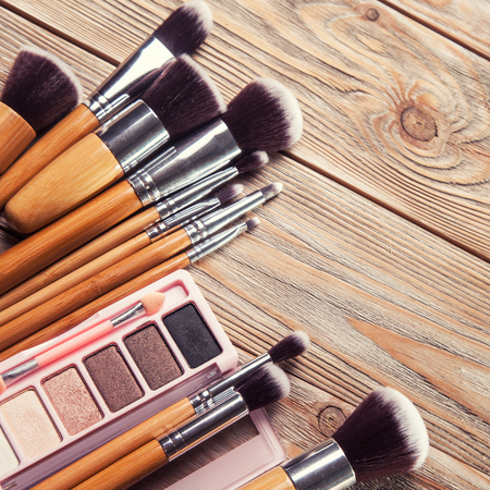 eye care professional: Brushes with cosmetics scattered chaotically on wooden background