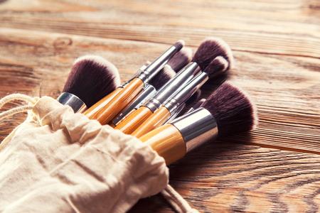 cepillo: conjunto de pinceles para el maquillaje dispersos caóticamente sobre fondo de madera Foto de archivo