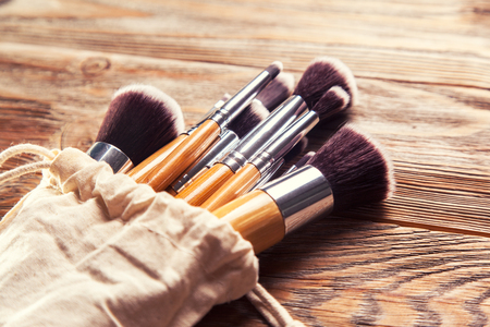 set of brushes for makeup scattered chaotically on wooden background Archivio Fotografico