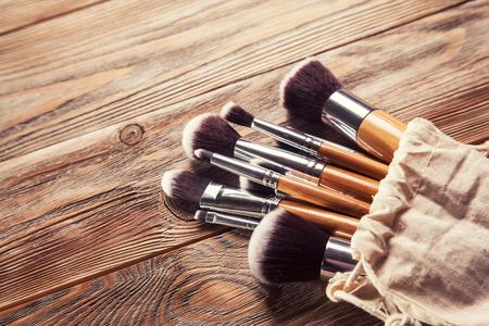 maquillaje de ojos: conjunto de pinceles para el maquillaje dispersos caóticamente sobre fondo de madera Foto de archivo