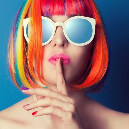 color hair: beautiful woman wearing colorful wig and white sunglasses against blue background