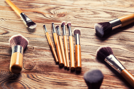 chaotically: set of brushes for makeup scattered chaotically on wooden background Stock Photo